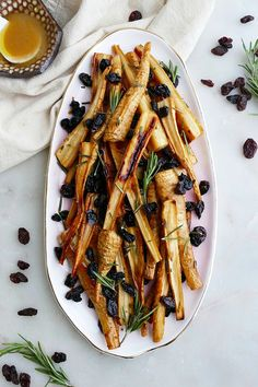 Honey Roast Parsnips and Raisins - a delicious vegetarian side dish with sweet glazed parsnips, fresh rosemary, and raisins! Make this simple recipe for Thanksgiving, Christmas, or just a weeknight dinner. Vegetarian Side Dishes, Best Vegetarian Recipes, Veggie Dishes, Vegetable Roasting Times, Honey Roasted Parsnips, Roasted Vegetable Recipes, Herb Recipes, Dinner Recipes, Roasted Veggies Recipe
