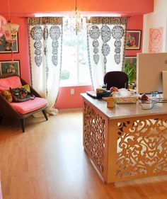 cool carved wood desk + peachy pink walls + cozy chair + pretty chandeliers + asian art prints