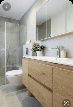 In this modern ensuite bathroom there is a glass surround shower with light colored tile. The wood cabinets and drawers below the white sink provide plenty of storage for toiletries. Ensuite Bathrooms, Bathroom Renos, Bathroom Renovations, Bathroom Storage, Small Bathroom, Bathroom Ideas, Bathroom Organization, Budget Bathroom, Bathroom Vanities