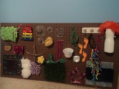 The OT Mama: DIY Sensory Board. I like the addition of a noise maker. I've also seen mirrors, tap light and dangled chains. This one is on a peg board, but why not just use a cardboard box-easier to travel with too! Diy Sensory Board, Sensory Wall, Sensory Rooms, Autism Sensory, Baby Sensory, Sensory Bins, Sensory Activities, Activities For Kids, Motor Activities