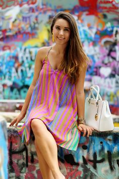Rainbow striped dress at Graffiti park in Austin, TX (Hope Outdoor gallery); white handbag; yellow tassel earrings; wedges; summer style; cute look; colorful