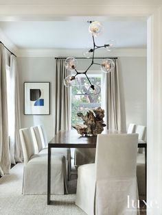 Custom slipper chairs by Roberto Barahona Co. join a sculptural pendant light by Lindsey Adelman in this dining room, where furniture was scaled and customized to accommodate maximum seating for frequent entertaining.
