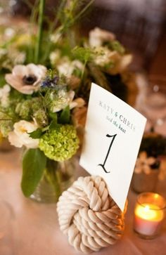 nautical knot table number in front of greenery centerpiece at nautical wedding.