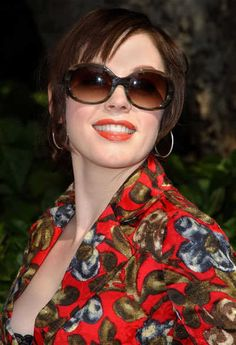 Rose McGowan posting with her ponytail hairstyle with bangs and sunglasses