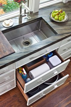 Exceptionnel Cabinets Accented With Nickel Handles Alongside A Dark Stone Counter Which  Frames An Undermount Sink With Sliding Chopping Board And Draining Rack  Paired ...