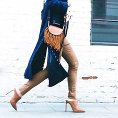 A long duster coat is paired with a Chloé fringe saddle bag, skinny pants, and mules