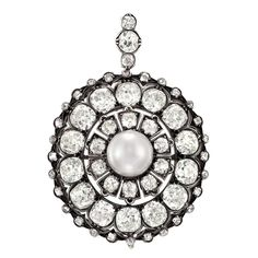 Antique Silver, Gold, Natural Button Pearl and Diamond Pendant. The circular pendant centering one button pearl approximately 8.95 mm., encircled and topped by 13 old-mine cut diamonds approximately 1.50 cts., further encircled by 14 old-mine and cushion-cut diamonds approximately 6.30 cts., edged by 28 small old-mine and rose-cut diamonds, with concealed pendant-hook.