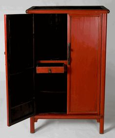 Also referred to as a noodle cabinet because the moldings surrounding the cabinet resemble a large thick noodle. The interior is divided into two sections. Great to use this cabinet as an entertainment center or media cabinet. Simple carved apron at the bottom of the cabinet between the legs. Decorative brass pulls on the doors and the drawers. Lovely red lacquered finish.