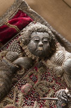 Detail of the tarnished gold and silver thread on an angel's face on the Lord Chancellor's purse at Wimpole