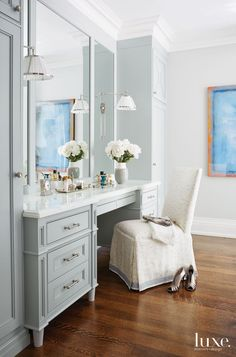 "This serene vanity space by Toronto designer Anne Hepfer is transformed with color. Benjamin Moore's Coventry Gray on the cabinetry acts as both statement-maker and pretty neutral against the softer walls painted in Benjamin Moore's Stonington Gray. ""The cabinetry is tailored but feminine, with some round detailing to maintain traditional character but in a cleaner more current design,"" explains Hepfer."