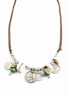 Made with cowrie shells, antique coins, vibrant turquoise and silver beads strung of super soft leather lace. This beautiful necklace has an adjustable sliding