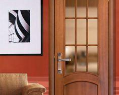 Es un juego de manillas en Niquel combinado con Bronce sobre una puerta caoba de un Salón.Su estilo moderno y ovalado es ideal para darle un toque elegante a su casa.