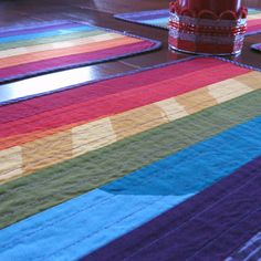 """Bring bright bold color to your table setting with a set of Marimekko placemats in the seven colors of the rainbow! Each placemat has red, orange, yellow, green, blue, indigo and violet Marimekko fabric strips sewn together and quilted onto a purple """"Sade"""" backing. The purple fabric is also used to bind the edges."""