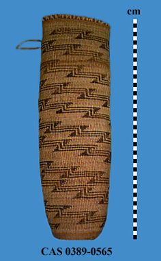 Cylindrical quiver with flat base and vertical sides; Woven primarily on 2-strand twining over tule cordage warps, with 3-strand twining of tule cordage wefts on base and just below rim; Warp ends are reinforced with rod and coil-wrapped in raffia; Designs on exterior sides consist of 2 broad zigzag lines that spiral very gradually from base to rim; Leather loop is attached at rim. Dimensions (cm)Height = 52.5, Max Diam = 17.5