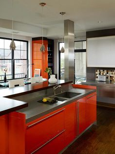 Looking anything but Halloween-centric, this stunning contemporary kitchen partners blaze-orange cabinets with both black and gray slab countertops. Black-frame windows integrate dramatic pattern into the scene. Steel-mesh pendants and a stainless-steel column add sophisticated shine, albeit with entirely different textures.