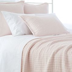 """With its pale blush hue and soft ribbed weave, this cotton matelassé coverlet adds a touch of femininity to classic white and ivory beds, or layers beautifully with florals and patterns. • 100% cotton. • Stone washed. • Knife edge. ½"""" top hem, 1"""" side hem. • Made in Portugal."""