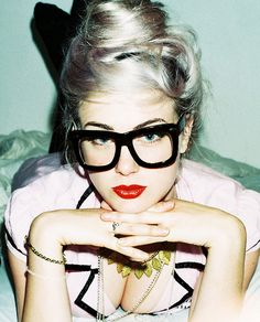 Bow, platinum hair, giant glasses, red lipstick, pink/black piped shirt