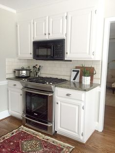 painting kitchen cabinets white + granite countertops + light gray walls