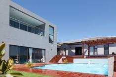 Outdoor living, Timber wood deck patio, crystal blue clear swimming pool with fountain spout waterfall features, pool landscaping, built-in planters, Covered stretch tent Gazebo, Timber pergola, outdoor entertainment space, sliding doors, lawn, double storey home, windows, deck steps levels, backyard garden, 162 on Sunbird, Langebaan, West Coast, South Africa Construction Architecture Interior Design Development Turnkey House Home Building Property Development Turnkey Services Architecture Ideas Property Development, Design Development, Deck Patio, Backyard, Timber Pergola, Deck Steps, Waterfall Features, Interior Architecture, Interior Design