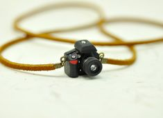 Personalized necklace Nikon D600 Camera miniature / personalized gift / personalized necklace / personalized jewelry  Created in a black polymer clay, little resin and real photo. This DSLR camera model is Nikon D600. The Picture of LCD is real. The surface of photo is covered with strong and clear resin. Necklace string is real leather(suede) This miniature camera is accessory, it is not work.  Choose model and Necklace type at option menu.  Size: Body : 2.3 cm * 1.8cm * 1cm Lens : 0.8cm…