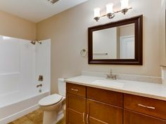 La Jolla Condo Bathroom remodel with tan and brown tile floors, medium stained wood vanity with modern pulls, light countertops, a framed mirror and new lighting.