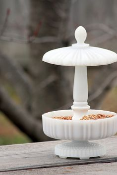 I LOVE the way she took a milk glass candy dish, added a candlestick and made a bird feeder!  (Oh, that's a lamp part on the bottom - where to find that?)