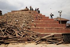 """People stand on top of a damaged building in Durbar Square in Kathmandu, April 26, 2015. The historic Durbar Square, a UNESCO world heritage site, was severely damaged in the earthquake.<br><br>From <a href=""""http://time.com/3840421/nepal-earthquake-aftermath-photos/"""">""""Witness the Aftermath of Nepal's Devastating Earthquake""""</a>"""