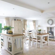 Open-plan white kitchen with island and dining area