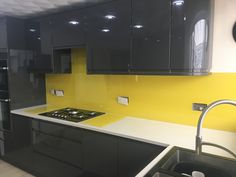 Bespoke bright yellow glass splashbacks with complimentary matching hot plates.