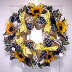The Sunflower Yellow & Black Wreath isa classic French summer wreath. Burlap paper mesh isthe background for the yellow, white & black color story of