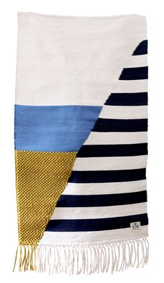 A rug made by an artisan weaver. Inspired by the beautiful San Sebastian beaches. Coloured awnings in classic blue and white stripes. Handmade as part of a limited edition set of 50. Made in Portugal