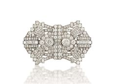 AN ART DECO DIAMOND DOUBLE-CLIP BROOCH Of openwork stylised buckle design, centred by two circular-cut diamond collets within a pavé-set diamond lozenge shaped surround, to a series of radiating millegrain-set old and French-cut diamond lines and similarly-set stepped frame, circa 1925