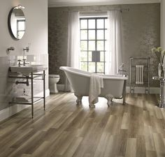 Delicate creams and natural wood flooring provide a gentle backdrop for the elegant shapes of our Savoy™ Victorian basin with stand and Salisbury roll top bath.  Bathroom suites