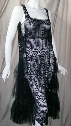Beaded sheer black 20s dress with iconic deco design.