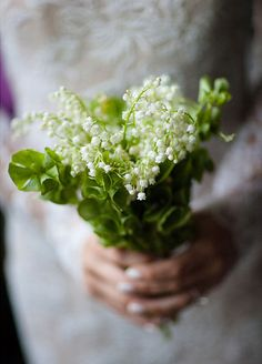 The bride picks an elegant small lily of the valley bouquet.