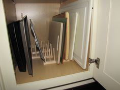 Tired of your favorite cookie sheet or the cutting board you need now ALWAYS being on the bottom of the stack? Use plate racks (available at Crate and Barrel) for an easily accessible storage solution.