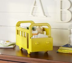 Crafted to resemble a familiar yellow school bus, this clever bin holds all your changing table essentials within easy reach. A compartment along the front corrals smaller items. Changing Table Storage, Baby Room Storage, Diaper Storage, Diaper Caddy, Changing Tables, Diaper Holder, Baby Boy Rooms, Baby Boy Nurseries, Kid Rooms