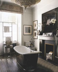 "Vintage inspired freestanding tub, dark wood fireplace, and layers of ""collected"" accessories make this a bathroom I certainly covet!"