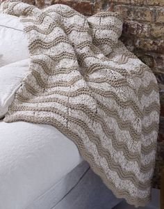 Free Knitting Pattern for Wave Afghan - This easy throw uses a simple lace stitch creates a great design with very little work. The pattern calls for 3 strands of Aran yarn held together and knit on size 13 needles. I think I would try knitting with 1 strand of bulky or super bulky instead. I think I'll make it for my mom