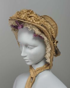 "Bonnet | Museum of Fine Arts, Boston — About 1855-1860. ""A taupe taffeta bonnet trimmed with cording and black lace, white lace ruching around face and under brim with bunches of minute lilies of the valley and purple double violets, narrow black satin ribbon ties at tips of brim, broad taupe taffeta ribbon streamers in center front, at top of brim a rosette of pinked self taffeta."""