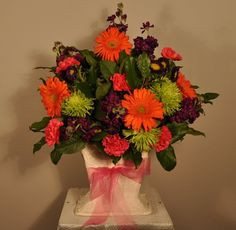 Vibrant Collection Ceremony Arrangement. Make your ceremony pop with one of these bright pieces on either side of your wedding ceremony.  Each large arrangement consists of large orange gerbera daisies, hot pink dianthus, lime green spider mums, purple matsumoto asters and stock and assorted greens nestled in an ivory container with a matching ribbon. For pricing visit our website
