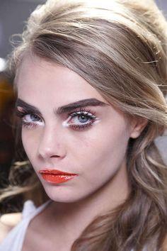 White eyeliner and glossy orange lips!