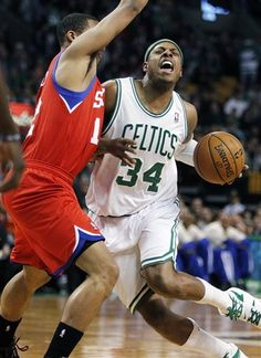Philadelphia 76ers' Evan Turner, left, blocks Boston Celtics' Paul Pierce (34) in the first quarter of an NBA basketball game in Boston, Sunday, April 8, 2012.