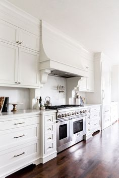 White French Kitchen Hood with Corbels and White Marble Slab Backsplash. White kitchen features white shaker cabinets paired with white marble countertops with gray veining and matching backsplash. A white French kitchen hood with corbels Kitchen Cabinets Decor, Kitchen Cabinet Design, Interior Design Kitchen, Home Design, Design Ideas, Kitchen Hood Design, Kitchen Vent, Kitchen Hoods, New Kitchen