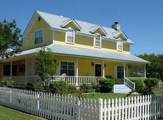 Love this home , picket fence, tin roof , Yellow! Love it.