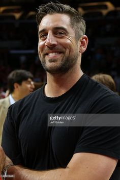 NFL quarterback Aaron Rodgers of the Green Bay Packers smiles as he stands on the court after the Wisconsin Badgers defeated the Arizona Wildcats 85-78 in the West Regional Final of the 2015 NCAA Men's Basketball Tournament at Staples Center on March 28, 2015 in Los Angeles, California.