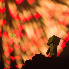 Robot figure standing in front of red heart shaped bokeh...