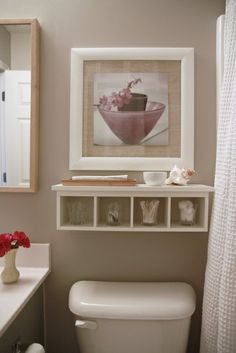 over toilet storage. Put under the picture already there. Fill with glass jars and some small items on top. Super cute.