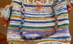 This chindi rag rug purse is the most colorful shoulder bag youll ever own!  Purchased a whole bunch of these rugs because for use in various spaces around the house, but they didnt look like I thought they would and of course it was past the time I could return them. So, they are now repurposed into totes and crossbodies instead via a sewing machine and a lot of vintage fabric and fabric ribbon!  This bag measures 17 wide by 14 tall by 3 deep, making it big enough to carry everything you…