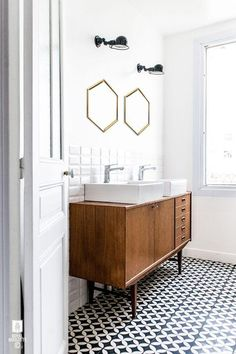 I love the look of the vintage vanity underneath the double twin sinks, paired with the bright white walls, bronze hexagon mirrors and tiny black and white penny tiles on the floor. Problem with using old cabinets or dressers into bathroom vanities is that they are often the wrong height. Gotta double-check for that when considering that kind of upcycle.